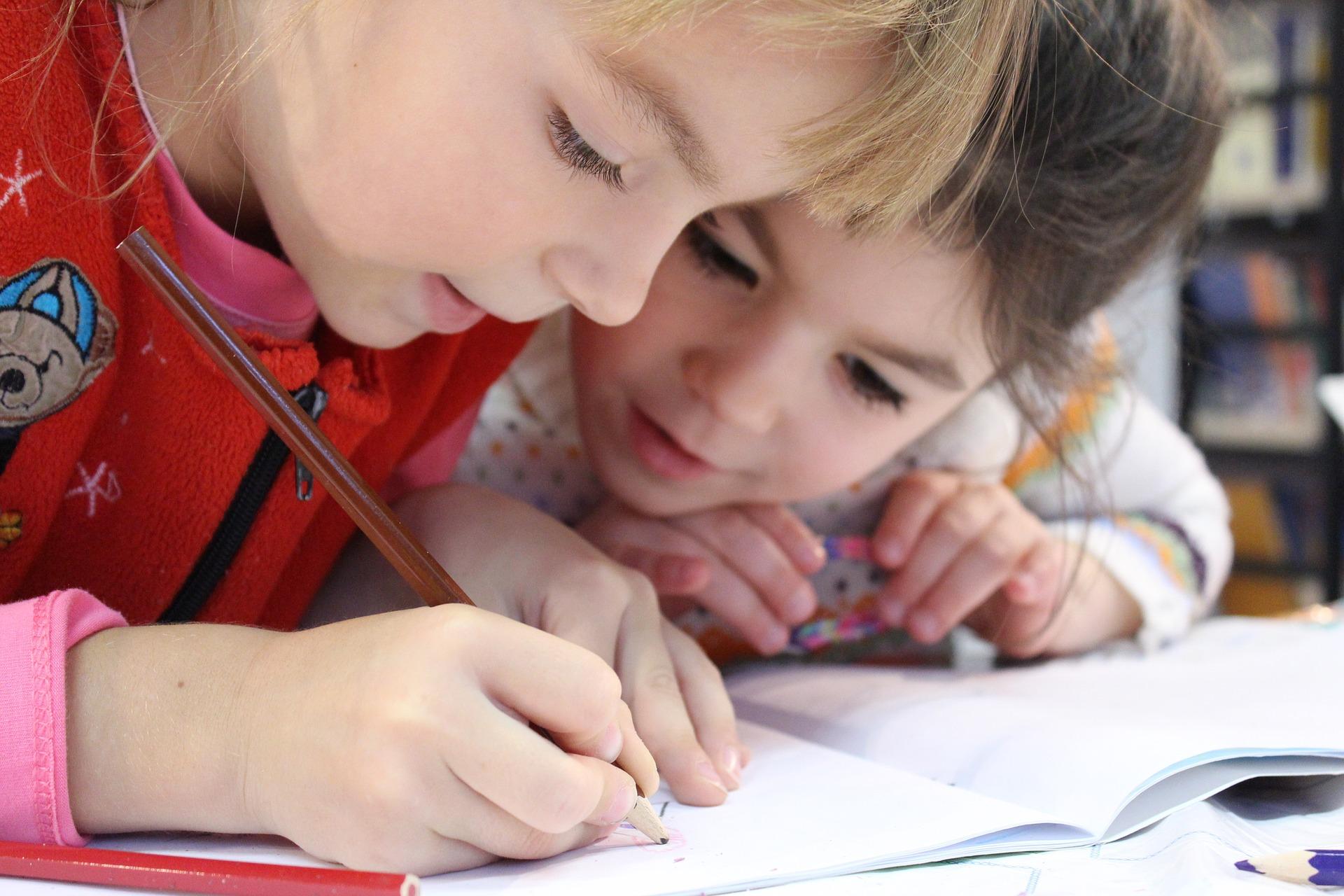 zwei Kinder schreiben in ein Heft und lösen eine Aufgabe - Kurse für Hochbegabte