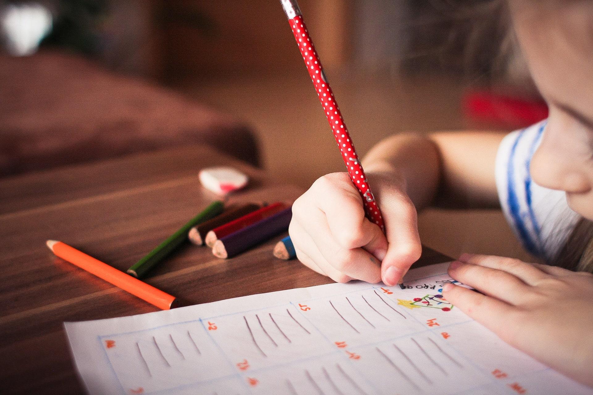 Kind schreibt in Heft - Begabungsdiagnostik in angenehmem Umfeld