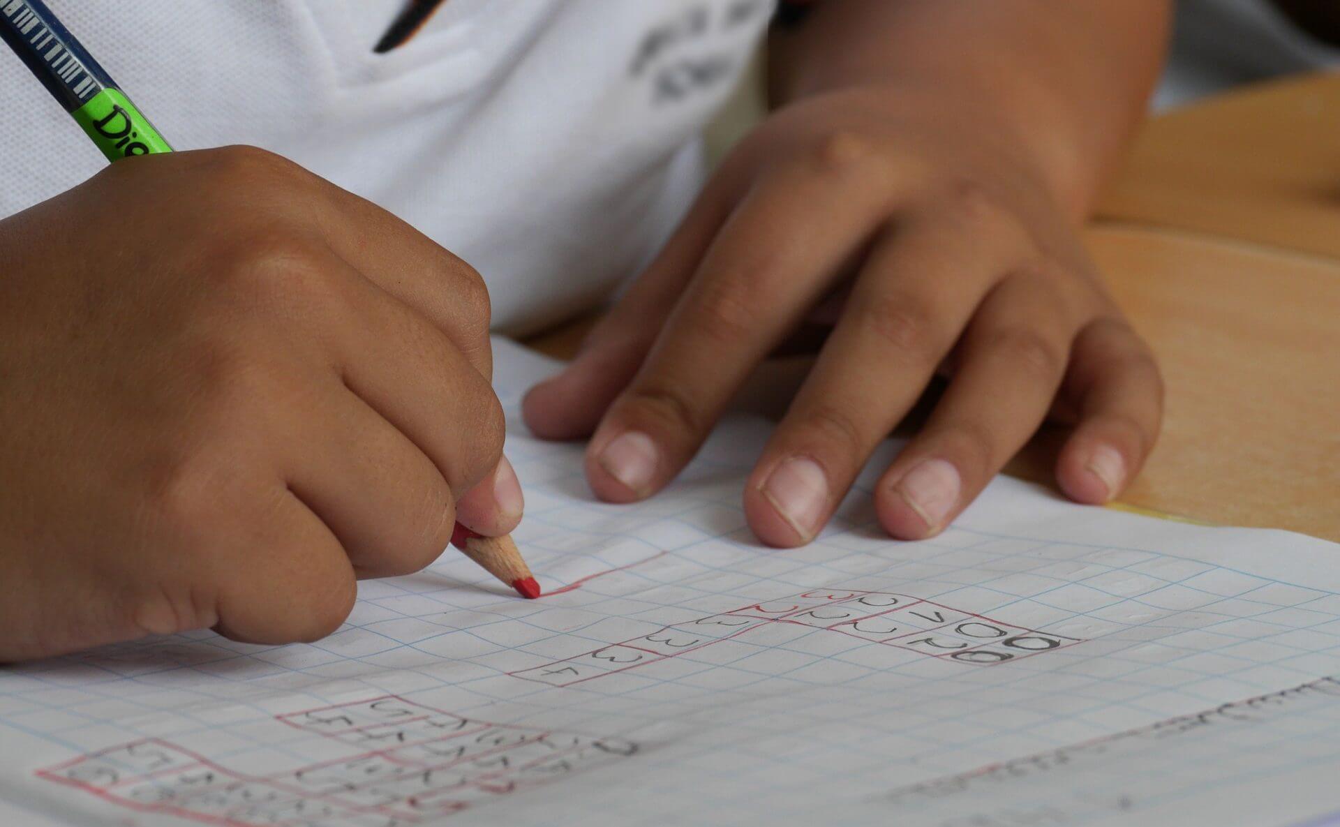 Kind schreibt mit Buntstift