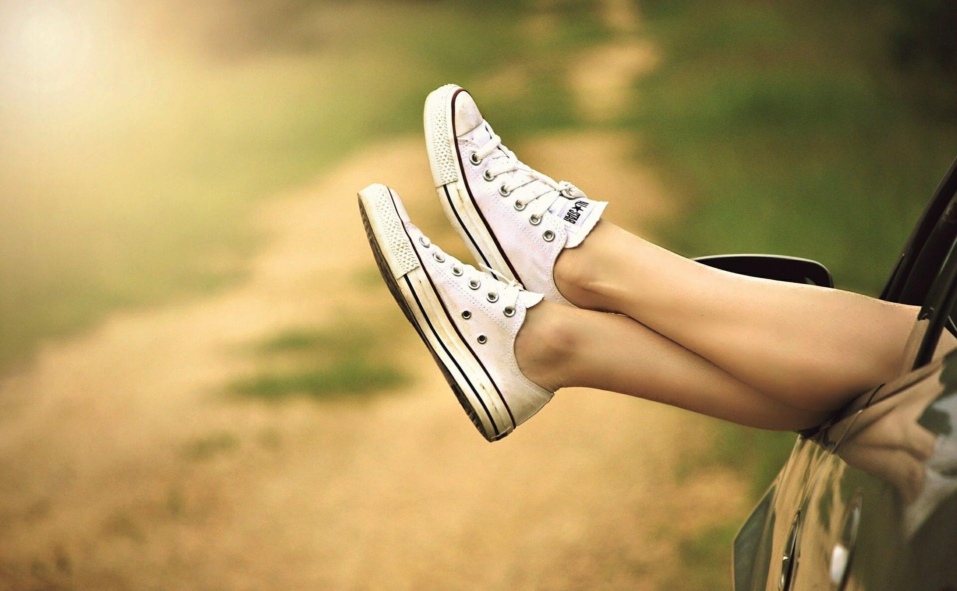 entspannte Füße werden aus einem Autofenster gestreckt