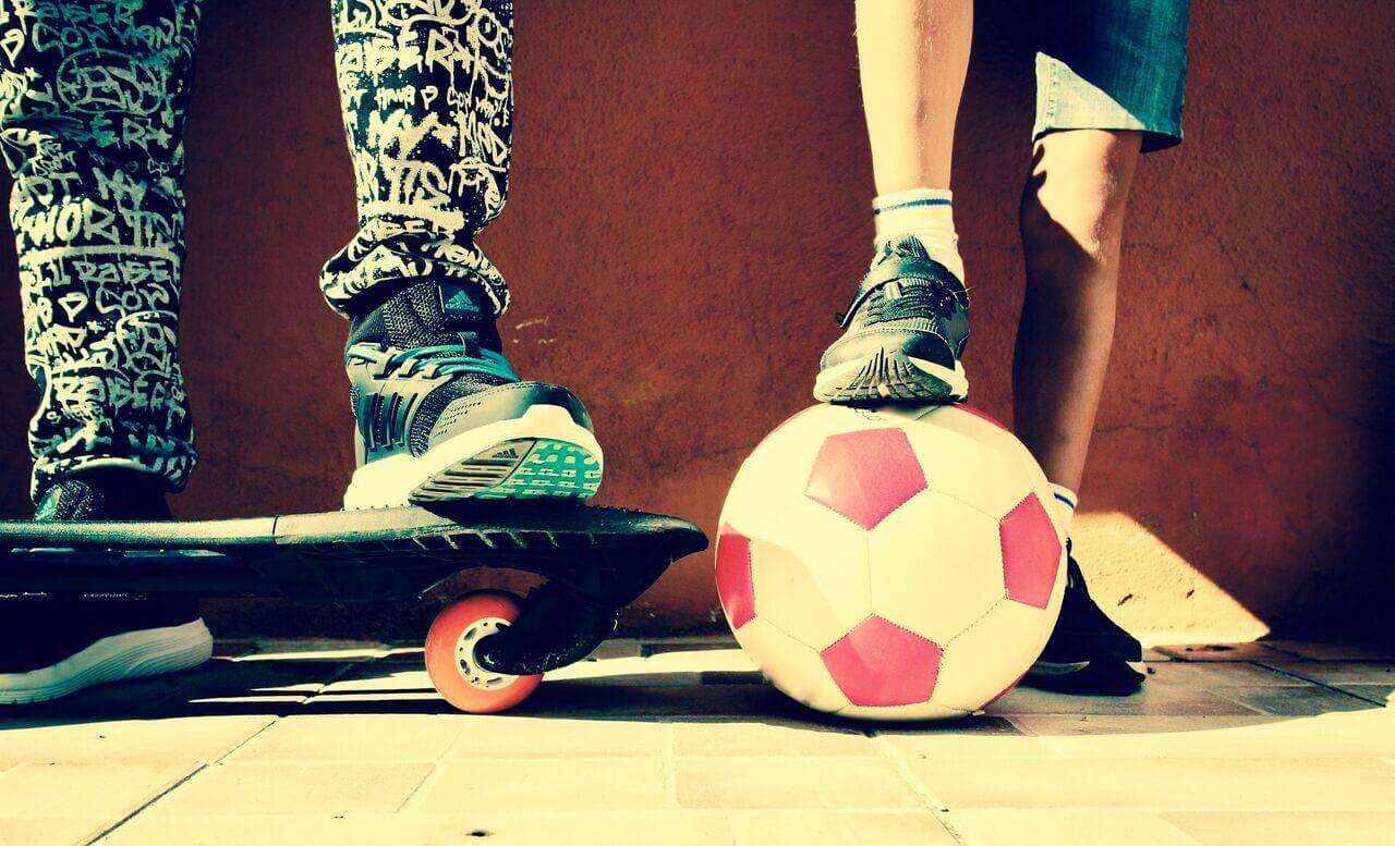 Schuhe und Skateboard von zwei Schulkindern